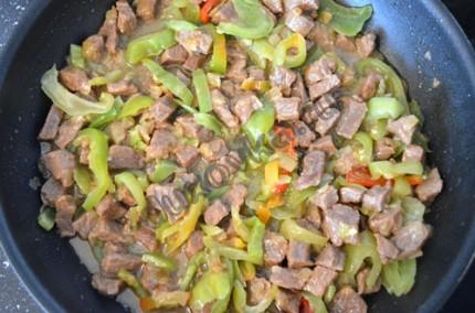 Фото: Шаг 5: Перец почистить, нарезать соломкой и выложить к мясу за 15 минут до его готовности